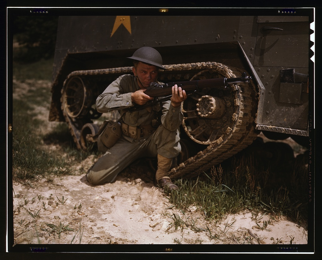 A young soldier of the armored forces holds and sights his Garand rifle like an old timer, Fort Knox, Ky. He likes the piece for its fine firing qualities and its rugged, dependable mechanism. Infantryman with halftrack