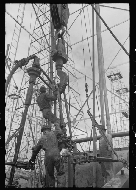 Activity at oil well; man on lengths of traveling block will be pulled up to the crown block at top of derrick, Kilgore, Texas