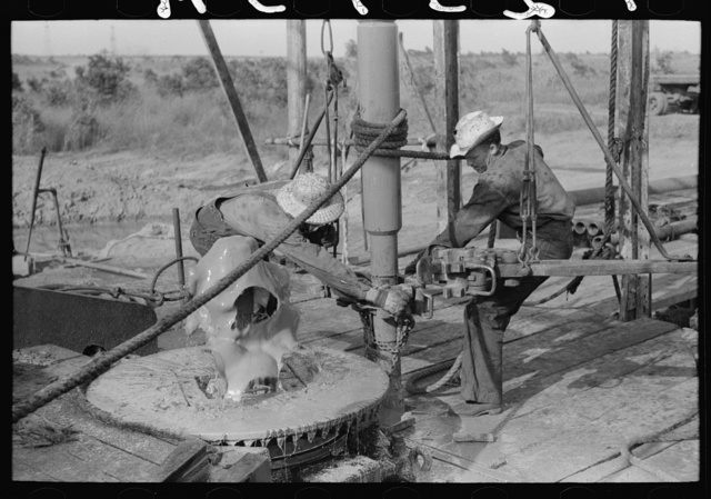 Adding a length of drilling pipe at oil well in Seminole oil field, Oklahoma. Wrench applied to loosen pipe