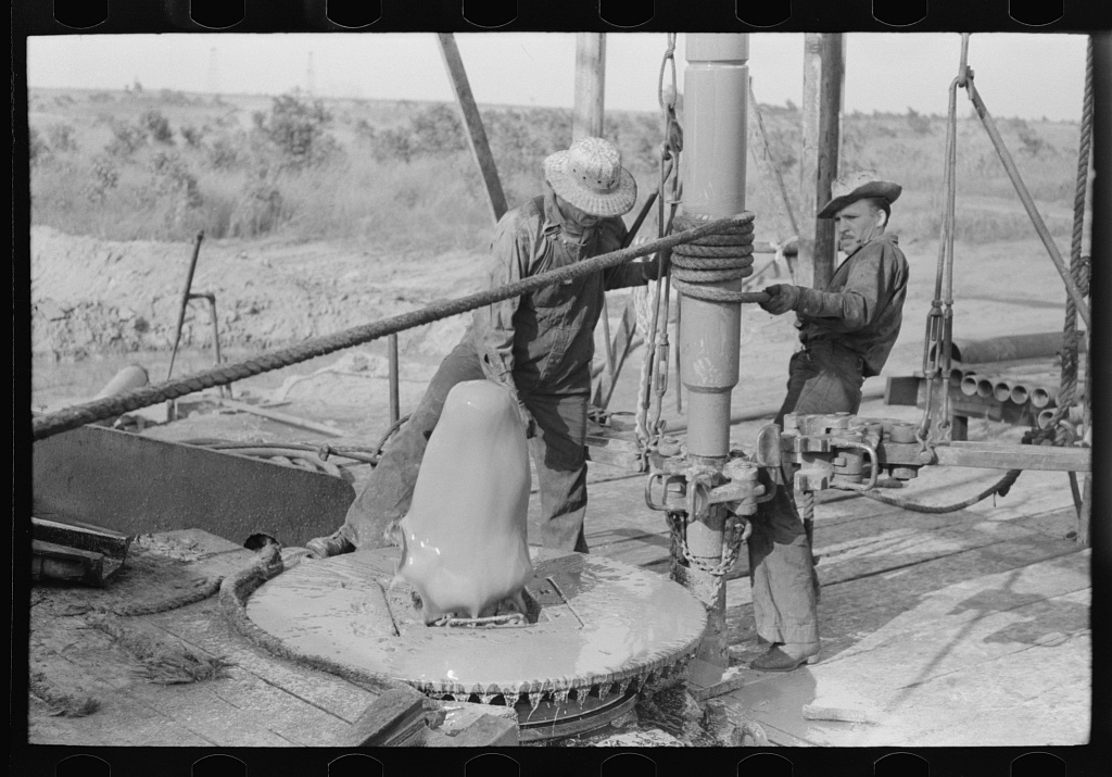 Adding a length of drilling pipe at oil well in Seminole oil field, Oklahoma. Lower end of traveling block is attached to pipe in rat hole by means of rope operated off winch