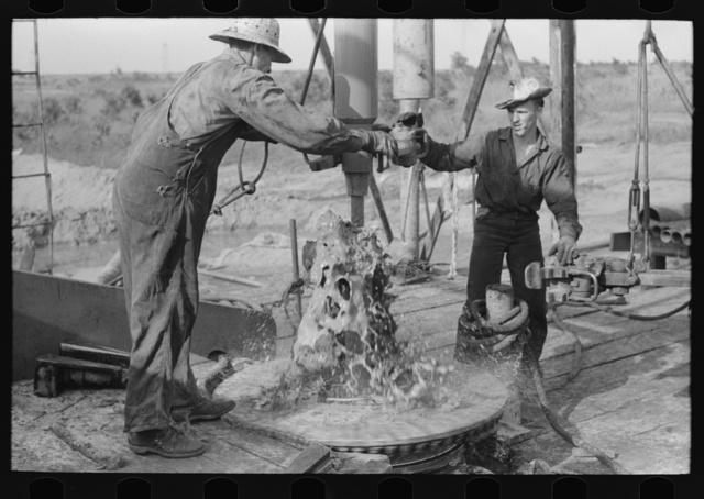 Adding a length of drilling pipe at oil well in Seminole oil field, Oklahoma. Mud spurting out as section of pipes are loosened