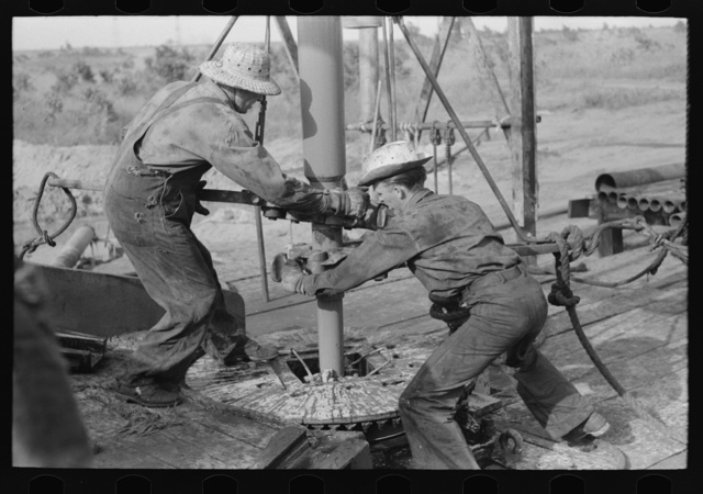 Adding a length of drilling pipe at oil well in Seminole oil field, Oklahoma. Wrenches applied to loosen pipe