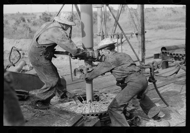 Oklahoma Historic Photos Adding a Length of Drilling Pipe at Oil Well in Seminole Oil Field Lower end of Traveling Block is Attached to Pipe in Rat Hole by Means of Rope Operated Off Winch