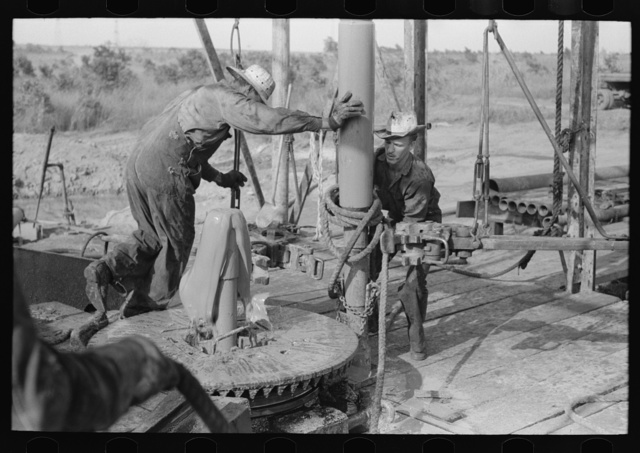 Adding a length of drilling pipe at oil well in the Seminole oil field, Oklahoma. Clamps are put in place; wrench applied to loosen pipe; mud spurting out as the sections of pipe are loosened; freed is moved over to rat hole; lower end of traveling block is attached to pipe in rat hole by means of rope operated off winch. This entire operation takes from twenty to thirty seconds