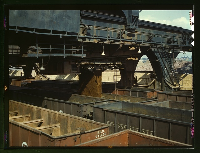 "After the ore is weighed in the ""Hewlett"" [i.e. ""Hulett""] machine it is dropped in the waiting hopper cars below; Pennsylvania R.R. iron ore docks, Cleveland, Ohio"