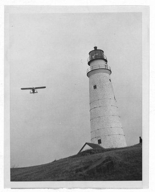 [Airplane, delivering Christmas presents, flys next to Boston Light on Brewster Island in Boston Harbor]