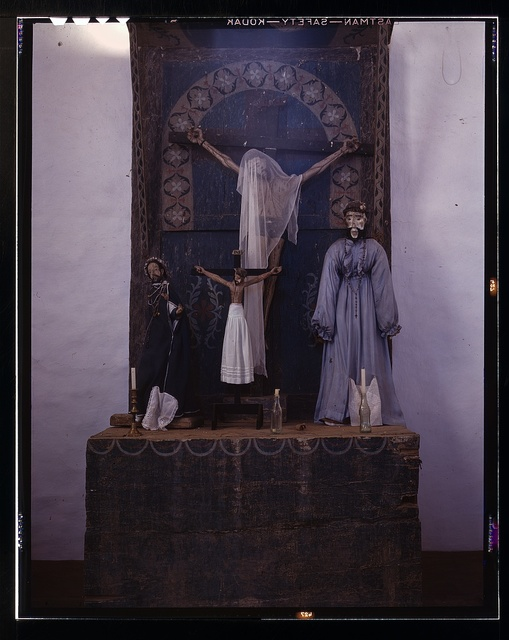 Altar in the church, Trampas, New Mexico. The prevailing colors are grey and blue. A Coca-Cola bottle is used as a candle holder