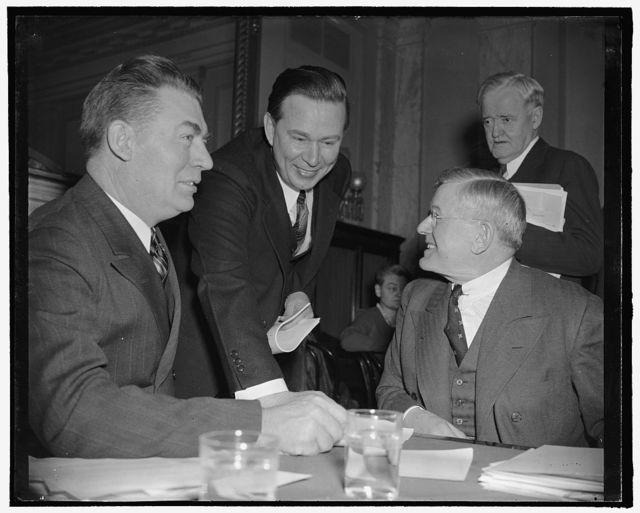 Amlie with committeemen investigating him. Washington, D.C., Feb. 6. With apparently no resentment toward committee members who are questioning his fitness for membership in the ICC, former Rep. Thomas R. Amlie posed with them. Left to right: Senator Edwin C. Johnson, Chairman, Amlie, Senator Clyde M. Reed in back, and Senator H.H. Schwartz, 2-6-39