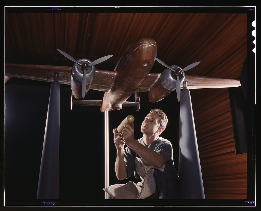 """An experimental scale model of the B-25 plane is prepared for wind tunnel tests in the plant of the North American Aviation, Inc., Inglewood, Calif. The model maker holds an exact miniature reproduction of the type of bomb the plane will carry. This plant produces the battle-tested B-25 bomber used in General Doolittle's raid on Tokyo, and the P-51 (""""Mustang"""") fighter plane which was first brought into prominence by the British raid on Dieppe"""