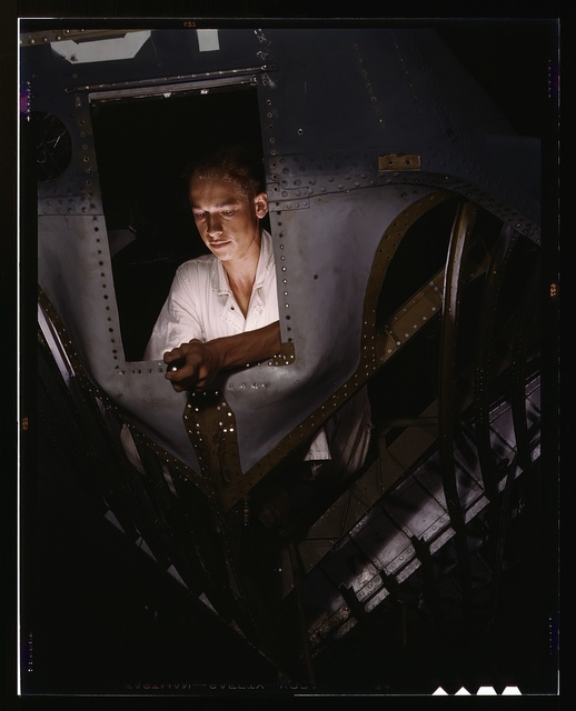 As an NYA trainee working inside the nose of a PBY, Elmer J. Pace is learning the construction of Navy planes, Corpus Christi, Naval Air Base, Texas