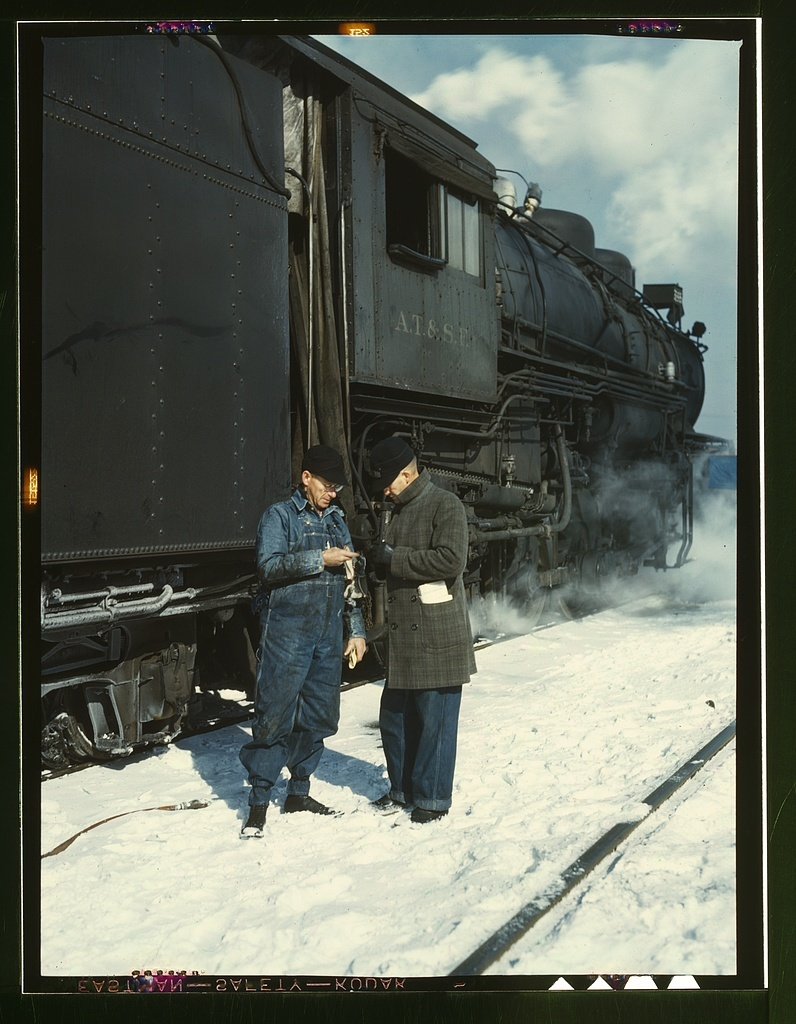 Atchison, Topeka, and Santa Fe railroad conductor George E. Burton and engineer J.W. Edwards comparing time before pulling out of Corwith railroad yard for Chillicothe, Illinois; Chicago, Ill.
