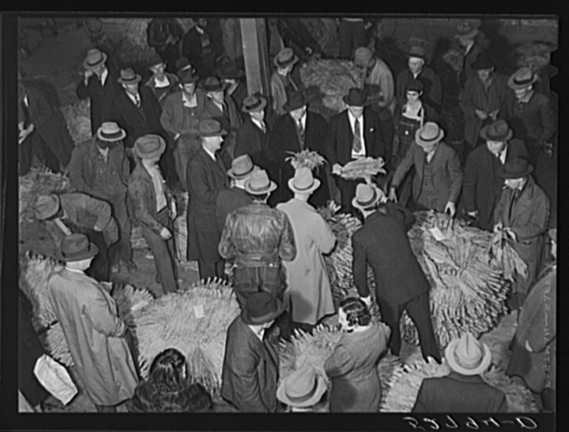 Auctioneer, buyers, and farmers during tobacco auction sale. Warehouse, Durham, North Carolina