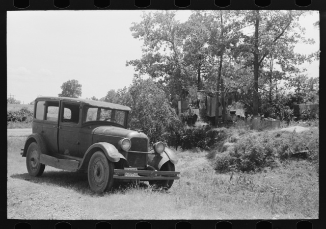 Automobile of family camped by the roadside while they did agricultural day labor in the neighborhood to secure funds to continue westward to Arizona and Califormia. This camp was near Spiro, Oklahoma