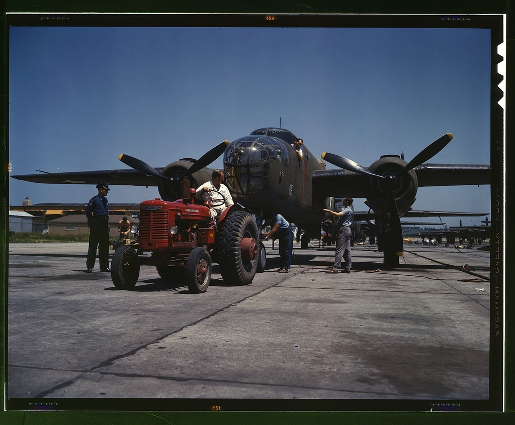 """B-25 bomber planes at the North American Aviation, Incorporated being hauled along an outdoor assembly line with an """"International"""" tractor, Kansas City, Kansas"""