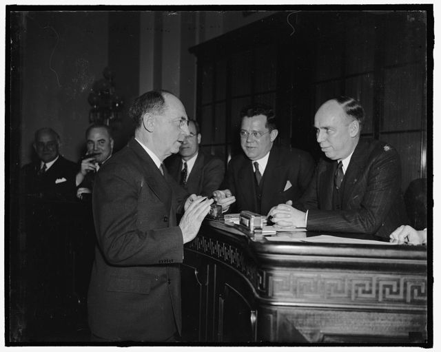 """Before Naval Affairs Committee. Washington, D.C., Feb. 7. Flatly denying any foreign commitments or understandings, Admiral William D. Leahy, Chief of Naval Operations, today told to Naval Affairs Committee of the House that the fleet expects """"To stand on it's own feet"""" in national defense, Interested listeners to the Admiral's testimony were Rep. Ralph E. Church of ILL. (center) and Rep. Ralph O. Brewster of Maine (right)"""