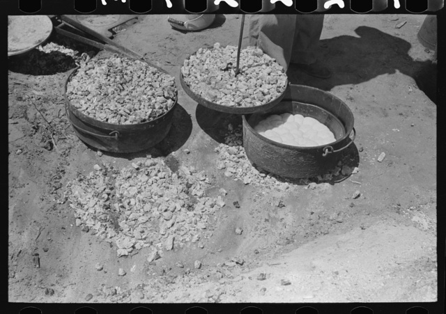 Biscuit being made in dutch oven on cattle ranch near Spur, Texas. Coals are piled on the lid of the dutch oven
