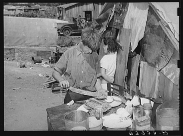 Boy living in camp near Mays Avenue making sandwich. This food is distributed by Saint Anthony's hospital after patients have been fed. This is the only foodline left in Oklahoma City, Oklahoma