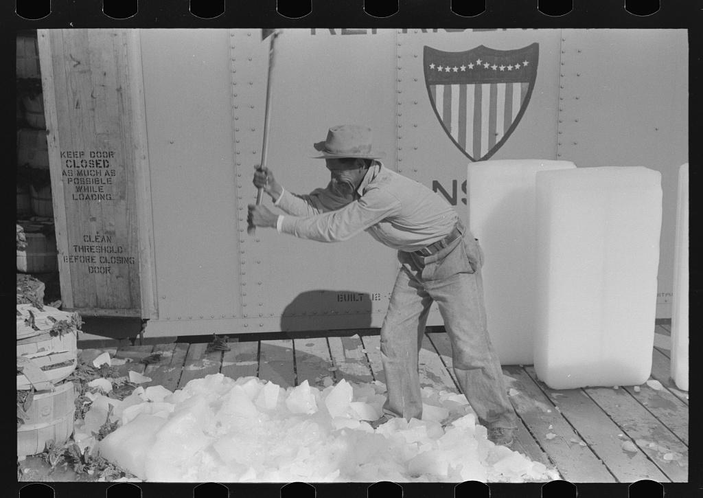 Breaking ice with flat side of ax, La Pryor, Texas
