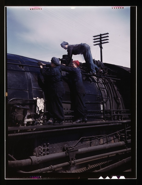 """C. & N.W. R.R., women wipers at the roundhouse cleaning one of the giant """"H' class locomotives, Clinton, Iowa"""