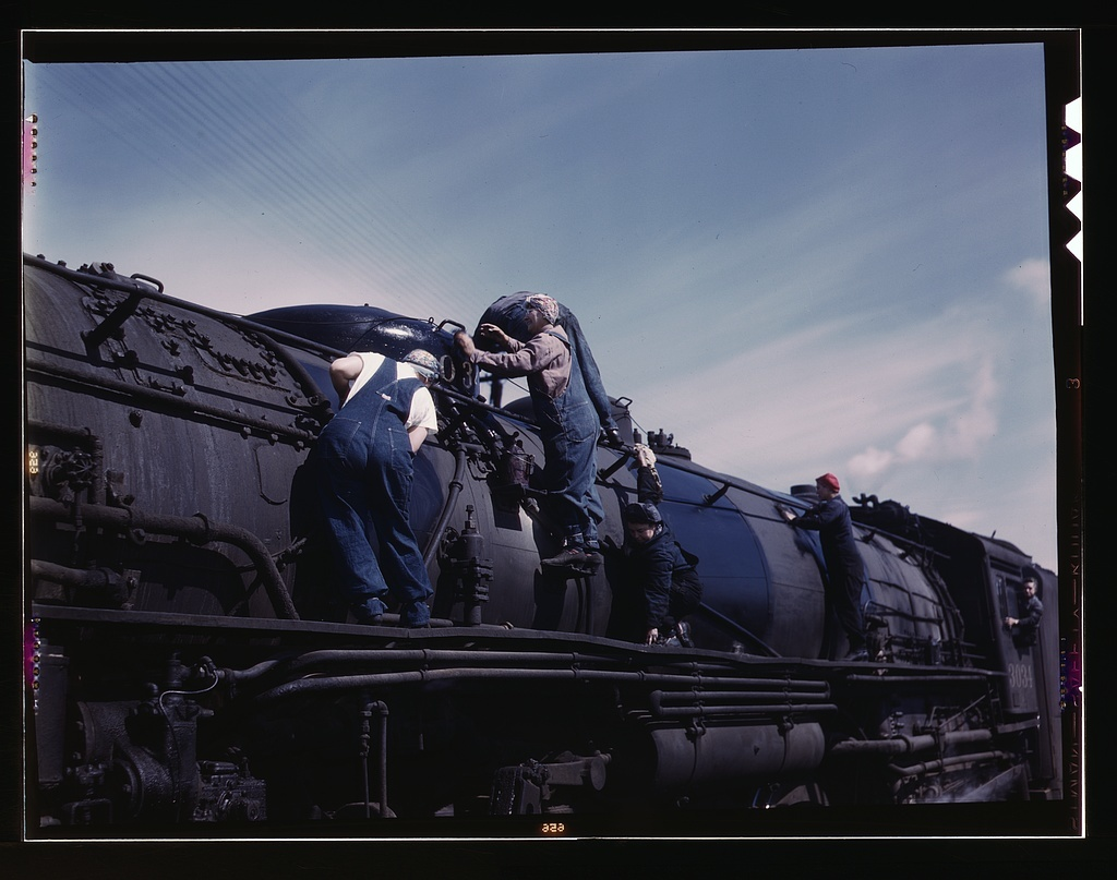 """C. & N.W. R.R., women wipers employed at the roundhouse cleaning one of the giant """"H"""" class locomotives, Clinton, Iowa"""