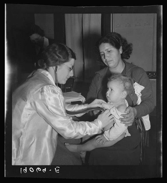 Calipatria, Imperial Valley. Visiting public health doctor conducts well-baby clinic in local school building adjacent to pea harvest. Many migratory mothers attend