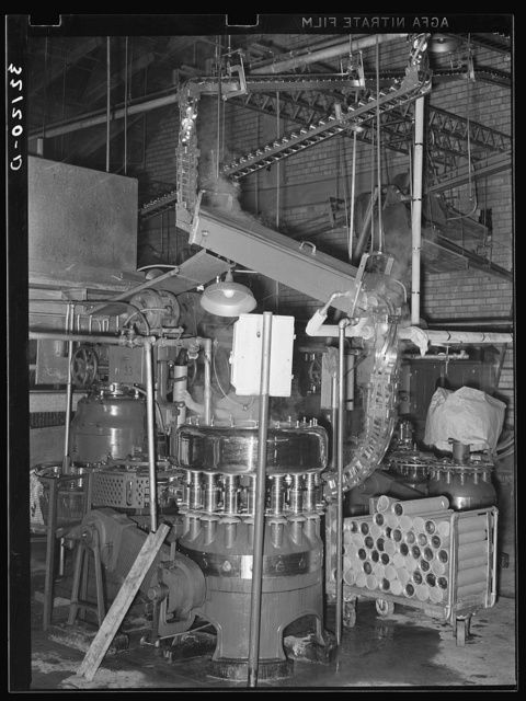 Cans are fed by gravity to a sterilizer and they are then filled in a rotary machine at the grapefruit juice canning plant. Weslaco, Texas