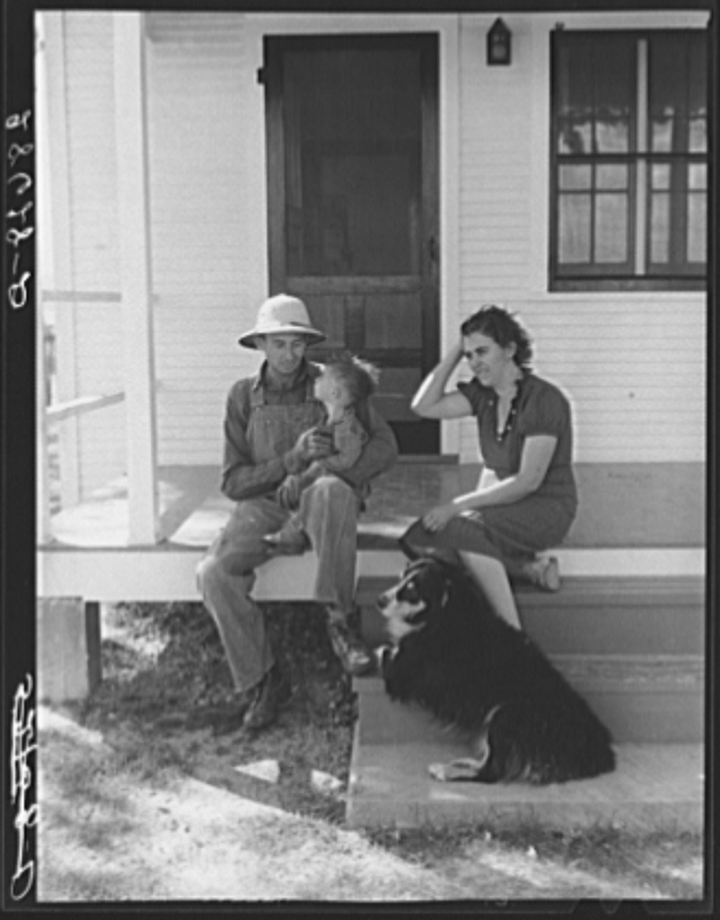 Carl Higgins family, purchase borrowers, on the porch of their home in Mesa County, Colorado