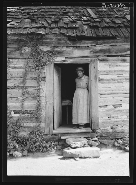Caroline Atwater standing in the kitchen doorway of double one and a half story log house. North Carolina