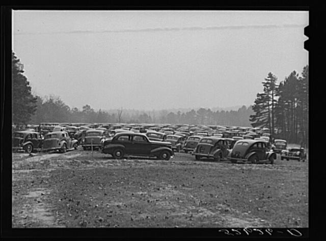 Cars parked in field near Duke University Stadium on day of Duke-Carolina football game. Durham County, North Carolina