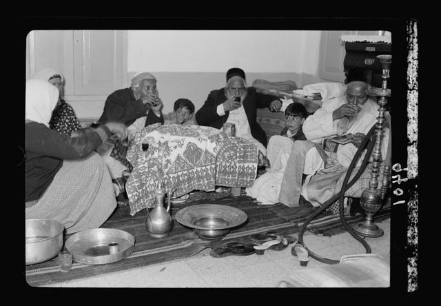 Ceremony of eating the Passover, Yemenite family, April 3, 1939. The meal covered while drinking the ceremonial wine