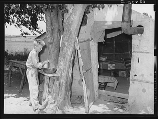 Child agricultural day laborer washing up in front of his tent home near Webbers Falls, Oklahoma. Muskogee County