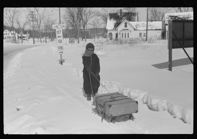 Child bringing home suitcase on sled, Franconia, New Hampshire