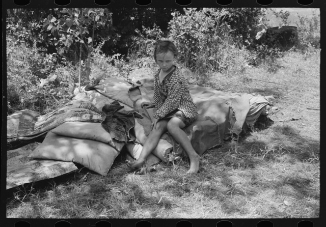 Child of agricultural day laborers camped near Spiro, Oklahoma. She is sitting on the bedroll. There was no bed in the camp. Sequoyah County, Oklahoma