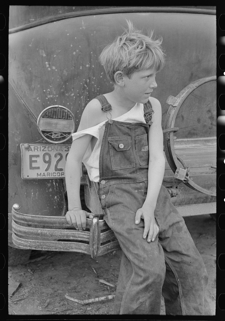 Child of white migrant worker sitting on bumper of their car from Arizona, near Harlingen, Texas