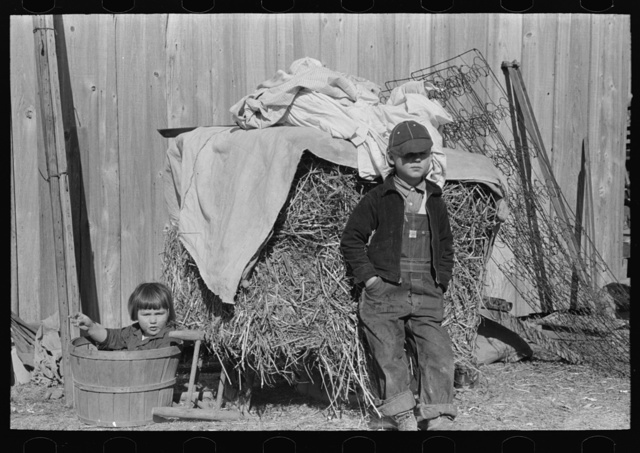 Children in front of household goods at side of house. These people came from a western parish and brought all their household goods for which they have no storage space in temporary housing provided at Transylvania Project, Louisiana