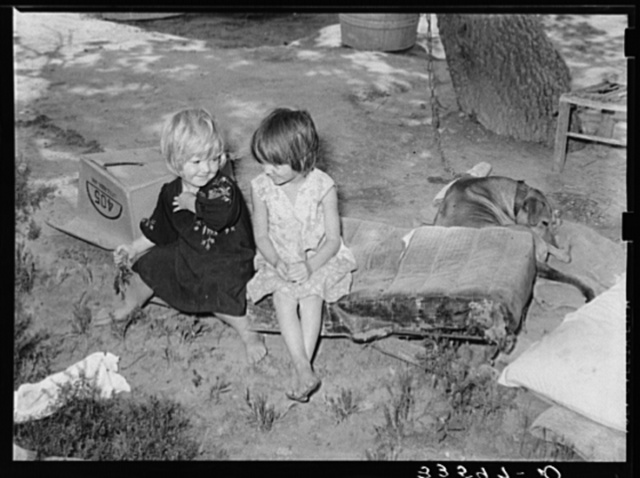 Children of agricultural day laborer sitting on an old automobile seat cushion. On Poteau Creek near Spiro, Oklahoma, Sequoyah County