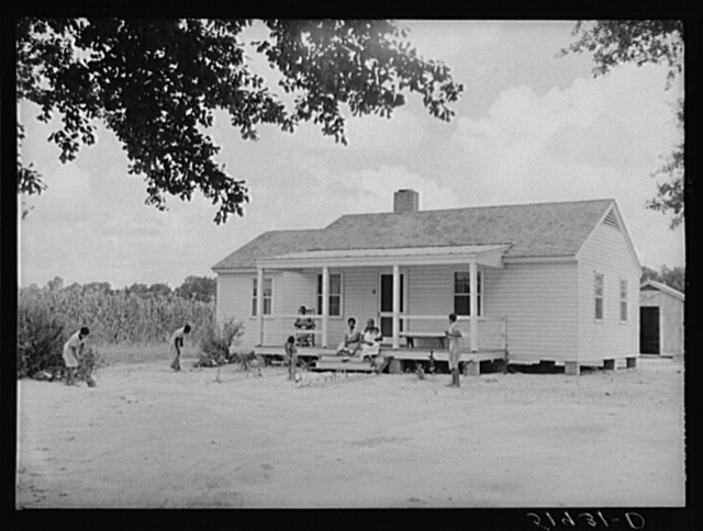 Children of Frederick Oliver, tenant purchase client, sweeping yard in front of new home. Summerton, South Carolina
