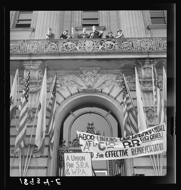 City officials hear the speeches made at mass meeting of Works Progress Administration (WPA) workers protesting cut in relief appropriation. In front of city hall, San Francisco, California