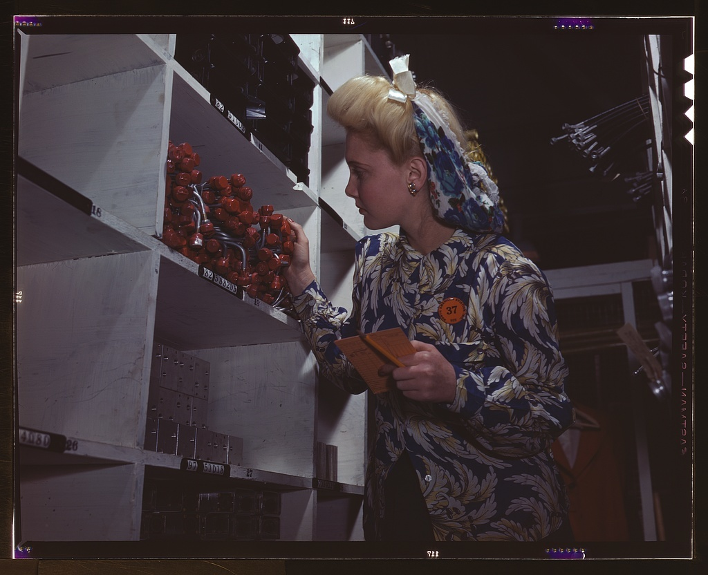"""Clerk in one of the stock rooms of North American Aviation, Inc., checking to see if the proper numbers of parts were received and placed in the proper bin, Inglewood, Calif. This plant produces the battle-tested B-25 (""""Billy Mitchell"""") bomber, used in General Doolittle's raid on Tokyo, and the P-51 (""""Mustang"""") fighter plane which was first brought into prominence by the British raid on Dieppe"""