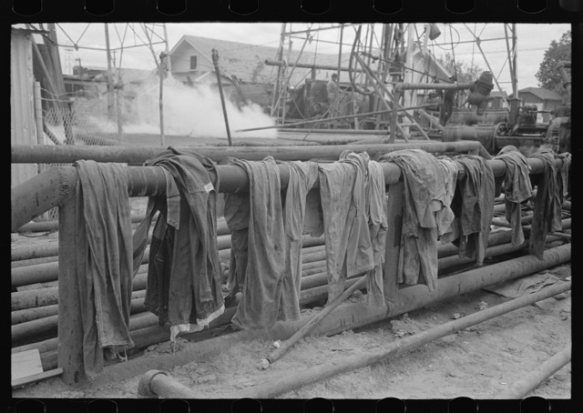 Clothing of oil drilling workers drying on steam pipe, Kilgore, Texas