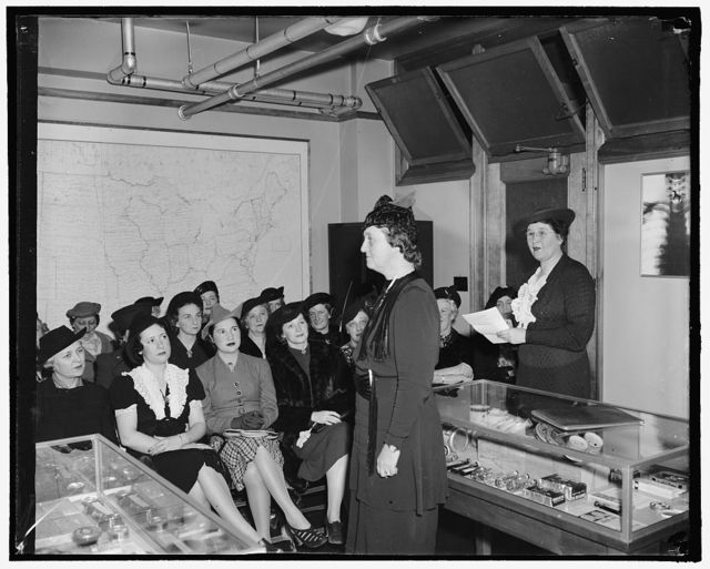 Congressmen's wives learn to speak in class. The Congressional Public Speaking class, composed of wives of congressmen, is attempting to teach the ladies to search out material and present it effectively under the direction of Mrs. Hugh Butler, public speaking teacher. They met today at the Agriculture Department's 'Chamber of Horrors' where Mrs. Ralph O. Brewster, wife of the member from Maine, gave her colleagues a sample of her learning while Mrs. Butler looks on from the right of the picture, 2-10- 39