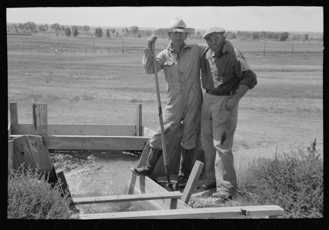 Cooperation in wells for irrigation purposes. Mr. Johnson and Mr. Wright, FSA (Farm Security Administration) clients, standing at the weir box, Syracuse, Kansas