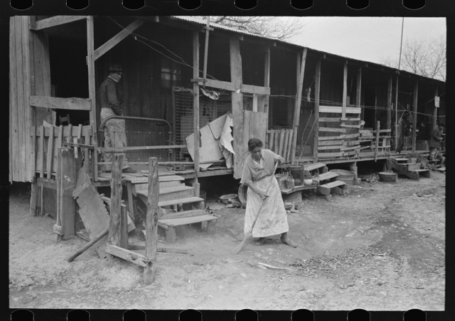 Corral, woman sweeping up trash, San Antonio, Texas