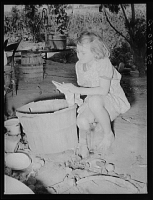 Daughter of migrant family wiping and packing dishes preparatory to leaving for California from Muskogee, Oklahoma