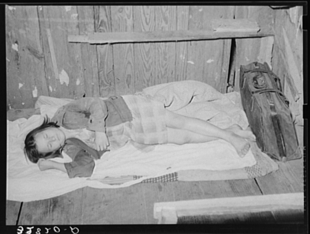 Daughter of migratory berry picker taking a nap on her bed on the floor.  Near Ponchatoula, Louisiana