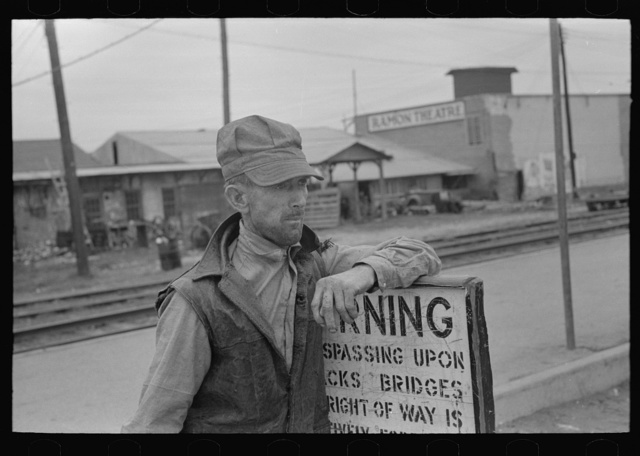 Day laborer resting on sign near railroad platform, Raymondville, Texas