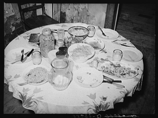 Dinner table of tenant farm family living near Sallisaw, Oklahoma. Food consists of beans, cornbread, lettuce, fried potatoes, fatback and gravy, cole slaw and sweet milk