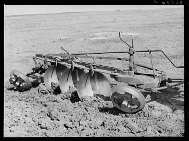 Disk plow drawn by tractor breaking virgin sod. El Indio, Texas