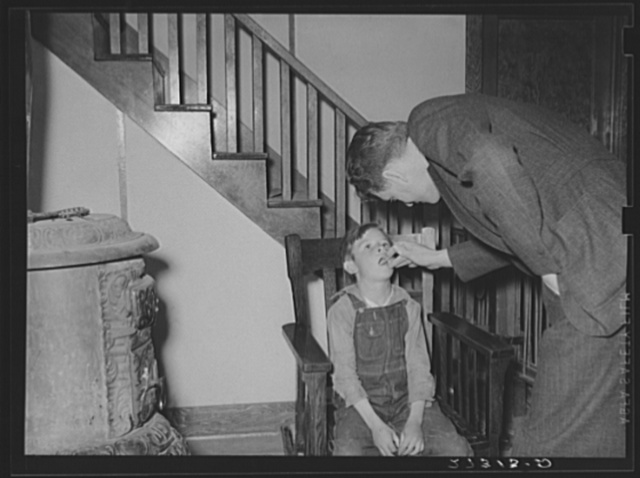 Doctor hired by farmers' cooperative health association examining a sick boy. Fairfield Bench Farms, Montana