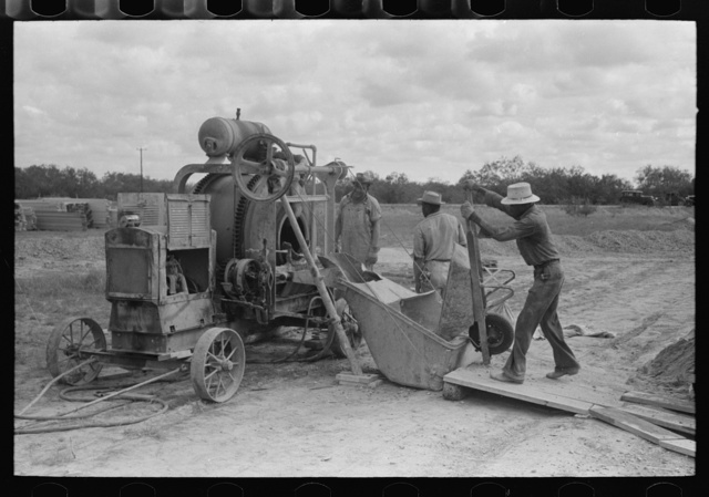 Dumping materials into concrete mixer at migrant camp under construction at Sinton, Texas